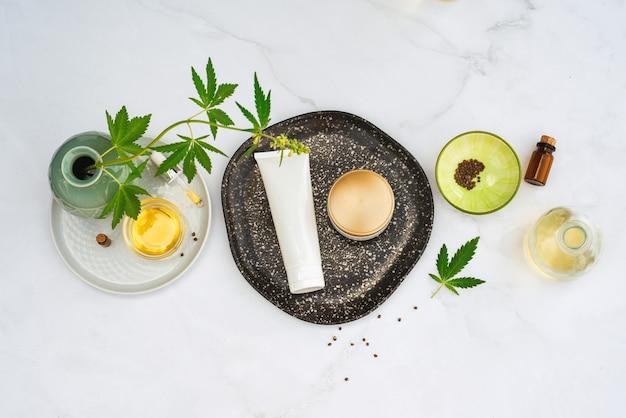 Tuba e barattolo di crema di olio di cbd, tintura di thc e foglie di canapa. lay piatto, minimalismo.