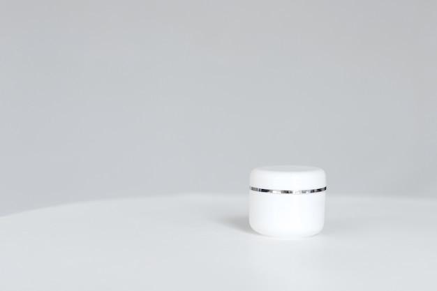 Crema tubolare su sfondo grigio tavolo bianco