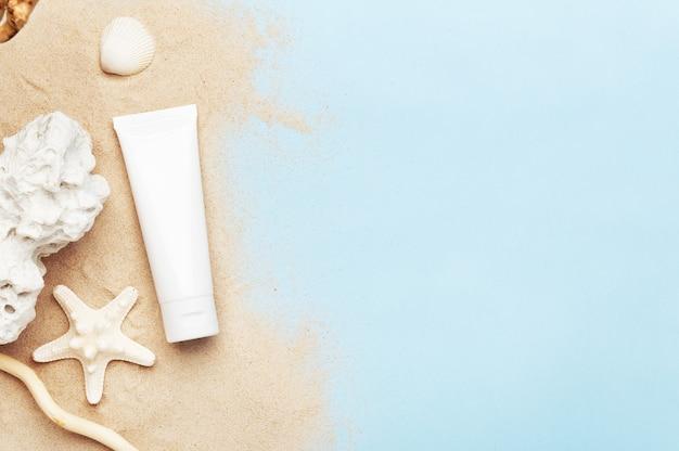 Tubo con crema per le mani, lozione per il corpo o crema solare. decorazioni estive come stelle marine, conchiglie e sabbia