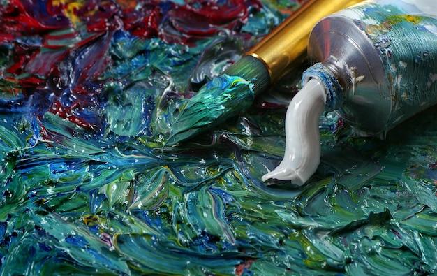 Tubo con pittura ad olio bianca e pennello su una tavolozza.