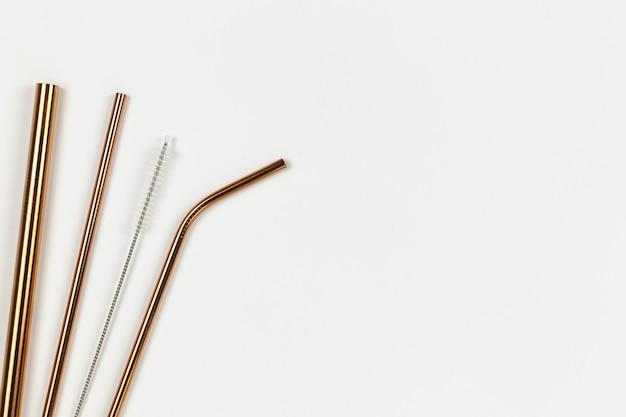 Tubi dall'opposizione di metallo riutilizzabile ambientale a tubi di plastica usa e getta. alternativa al concetto di stoviglie usa e getta. sfondo bianco. orizzontale. copia spazio. piatto disteso, primo piano, superiore veiw