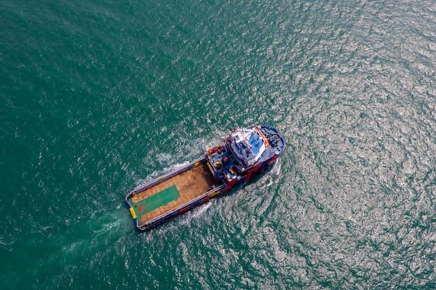 Barca del rimorchiatore che naviga sul mare verde