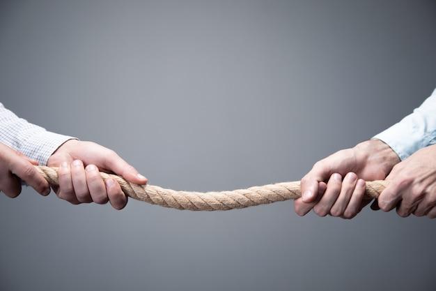 Tug war, due uomini d'affari che tira una corda in direzioni opposte.