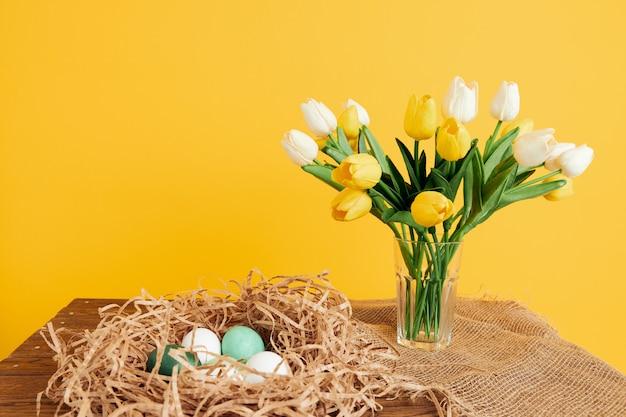 Uova di pasqua del mazzo del tulipano nella festa di tradizione del nido