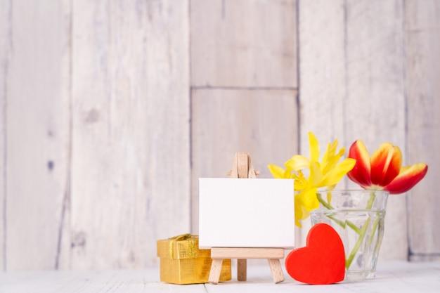 Fiore di tulipano in vaso di vetro con decorazione cornice su tavolo in legno parete di fondo a casa, primo piano, concetto di design per la festa della mamma.