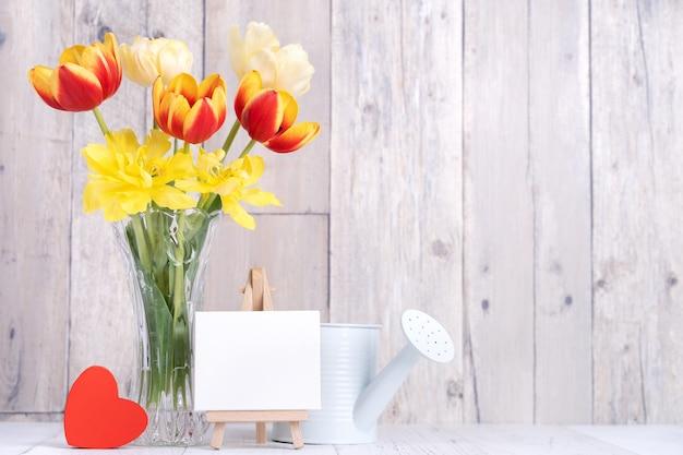 Fiore del tulipano in vaso di vetro con la decorazione della cornice sulla parete del fondo della tavola in legno a casa, primi piani, concetto di design di festa della mamma.