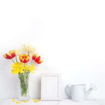 Fiore del tulipano in vaso di vetro con il posto della cornice immagine sul fondo della tavola in legno bianco contro il muro pulito a casa, primi piani, concetto di arredamento festa della mamma