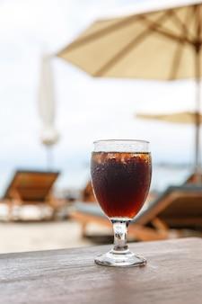 Bicchiere a tulipano con cola sul tavolo. ombrelloni da spiaggia