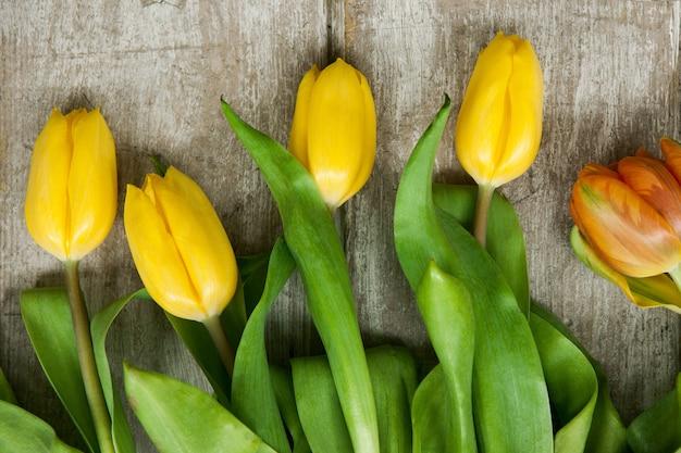 Mazzo della molla dei fiori gialli del tulipano su fondo di legno grigio. design carino per pasqua, 8 marzo, festa della mamma