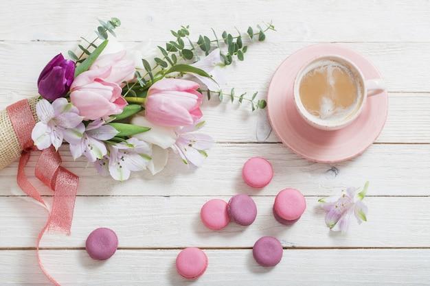 Tulipani e tazza di caffè con dessert. conc