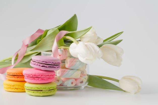 Tulipani e vaso pieni di marshmallow e macarons colorati