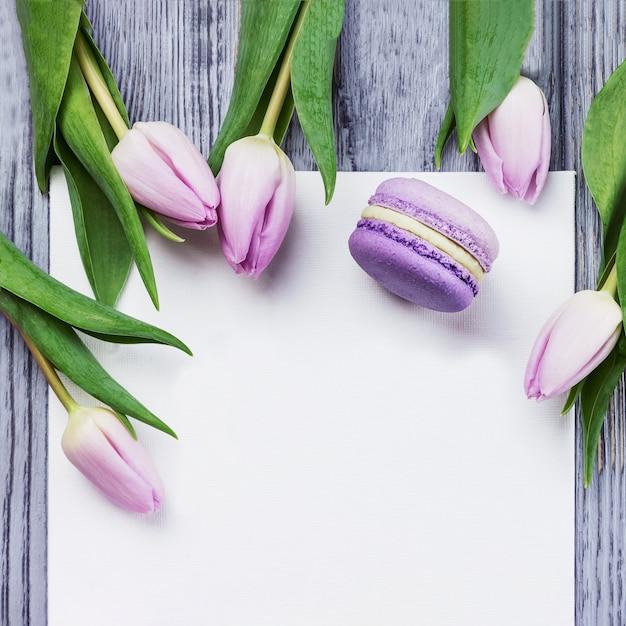 Tulipani, macaron viola e foglio bianco su un tavolo di legno grigio