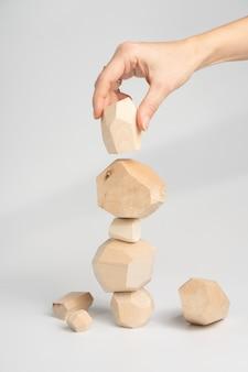 Tumi-ishi puzzle game. una donna o una ragazza pone la mano su un altro blocco di legno in cima a una torre instabile.