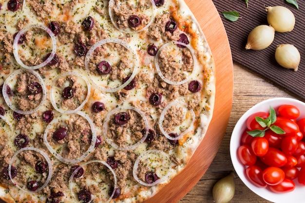 Pizza al tonno con cipolle, olive nere su un tavolo di legno con uva dolce e foglie di basilico