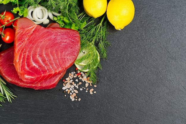 Tonno crudo bistecca di tonno sashimi di tonno affettato con verdure mangiare sano con frutti di mare cuciniamo a casa pesce carne layout su pietra nera