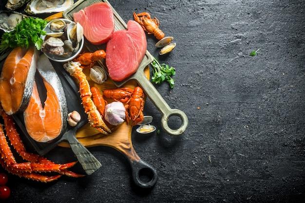 Bistecche di tonno e salmone su taglieri. sul nero rustico