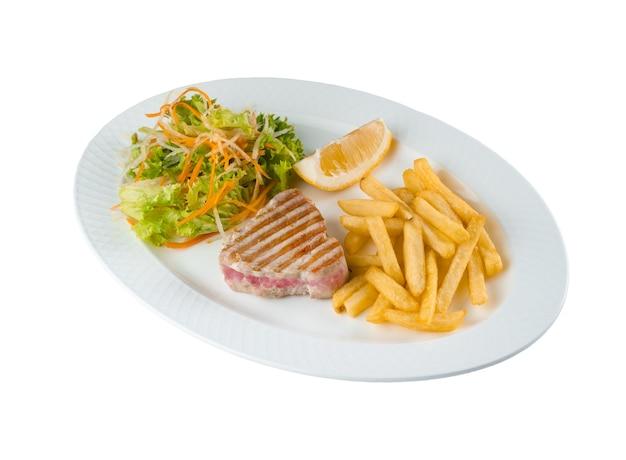 Bistecca di tonno alla griglia con insalata di patate fritte di carote, pastinaca, lattuga e limone su piatto bianco su sfondo bianco.