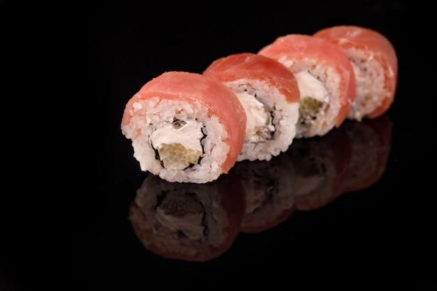 Rotolo di sushi di tonno su una superficie nera con la riflessione.
