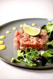 Tartare di tonno con insalata verde, lime, avocado e salsa di senape su piatto di ceramica. cucina raffinata, aperitivo al ristorante