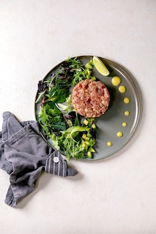 Tartare di tonno con insalata verde, lime, avocado e salsa di senape che serve su un piatto di ceramica sul tavolo di consistenza bianca. lay piatto, copia dello spazio. cucina raffinata, aperitivo al ristorante