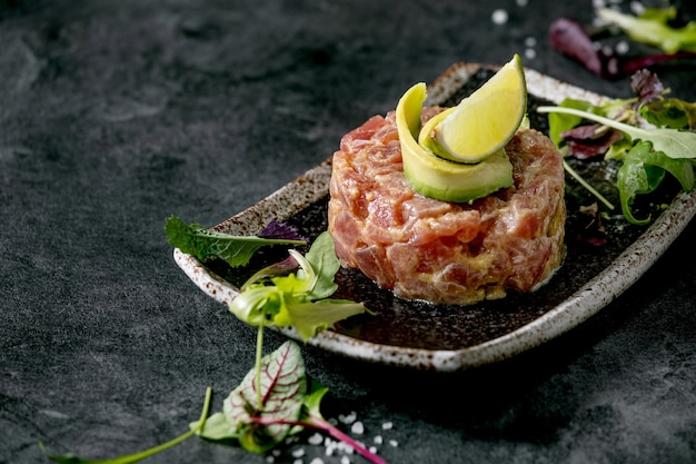 Tartare di tonno con insalata verde, lime, avocado e salsa di senape che serve su piatto in ceramica nera stile giapponese su sfondo di marmo nero. antipasto al ristorante. copia spazio