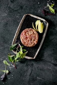 Tartare di tonno con insalata verde, lime, avocado e salsa di senape che serve su piatto in ceramica nera in stile giapponese sul tavolo di marmo nero. lay piatto, copia dello spazio. antipasto al ristorante