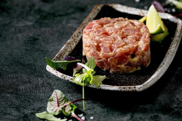 Tartare di tonno con insalata verde, lime, avocado e salsa di senape che serve su piatto in ceramica nera in stile giapponese sul tavolo di marmo nero. antipasto al ristorante. copia spazio
