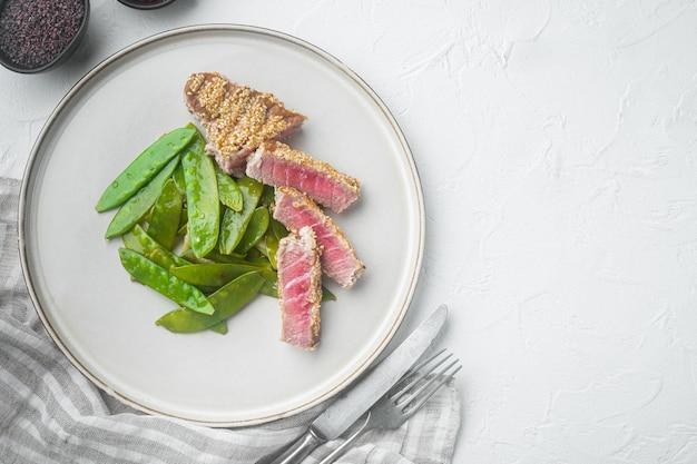 Antipasto di tonno tataki in crosta di sesamo con cipolline e piselli a scatto allo zucchero, su piastra, su sfondo di pietra bianca, vista dall'alto piatta, con copyspace e spazio per il testo