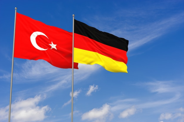 Bandiere della turchia e della germania sopra il fondo del cielo blu. illustrazione 3d