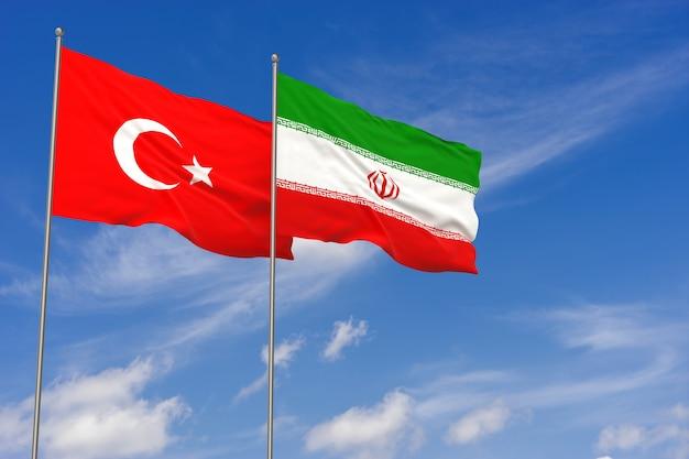Bandiere della turchia e dell'iran sopra il fondo del cielo blu. illustrazione 3d