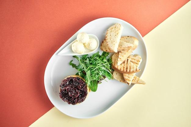 Patè di fegato di tacchino con cipolla confit, curtons in un piatto bianco su una superficie dai colori brillanti