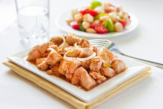 Spezzatino di tacchino in salsa di senape di pomodoro con cipolla su piatto quadrato e insalata di pomodori colorati in background