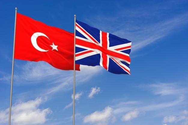 Bandiere della turchia e del regno unito sopra il fondo del cielo blu. illustrazione 3d