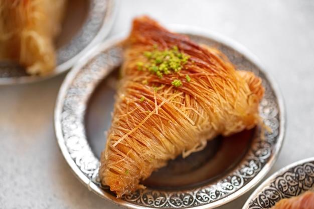 Baklava turco su piastra metallica orientale su tavolo bianco