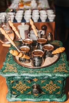 Caffè turco preparato sulla sabbia a cezve. orientale, caffè orientale