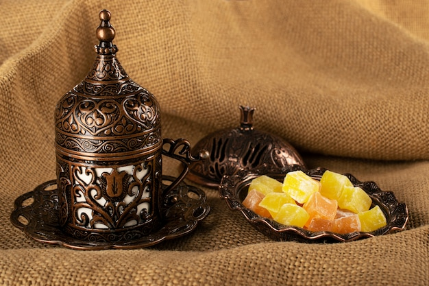 Caffè turco in pentole tradizionali di rame, delizia turca e tazza di demitassa