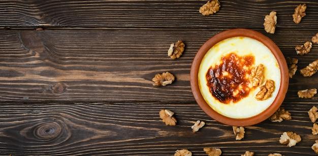 Varietà di dessert della cucina turca. budino di riso al forno - sutlac dessert turco al latte in casseruola di terracotta con noci. vista dall'alto con copia spazio