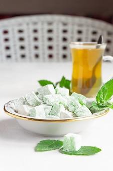 Lokum di delizia turca su un piatto con un bicchiere di tè