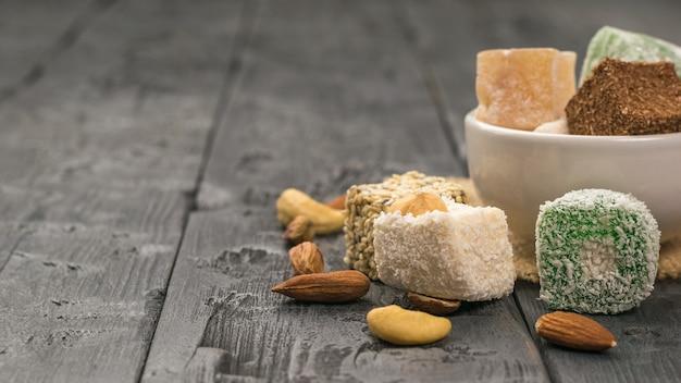 Delizia turca e noci in una tazza bianca su un tavolo di legno. dolci orientali. spazio per il testo.