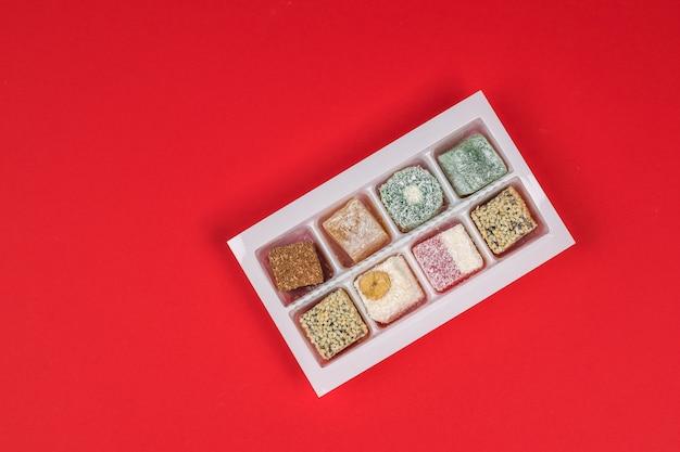 Delizia turca in un contenitore di plastica su sfondo rosso. dolci orientali. disposizione piatta.