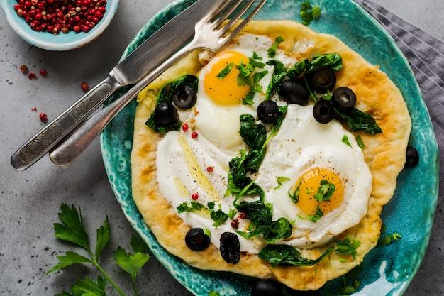 Focaccia di uova turche con yogurt, formaggio, olive, spinaci e peperoncino