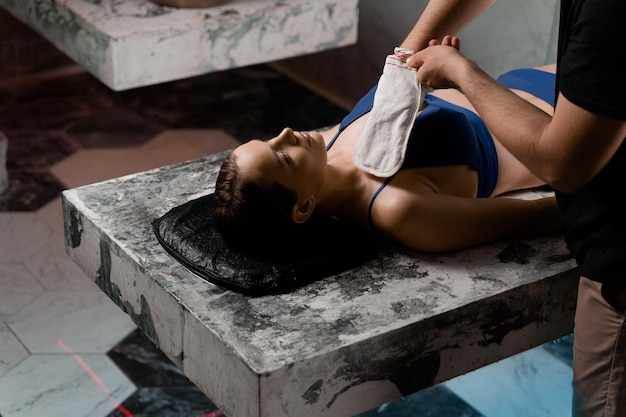 Massaggio turco con schiuma e peeling con guanto kese. relax nel centro termale. il massaggiatore sta facendo il massaggio.