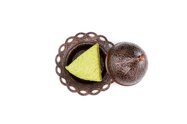 Halva turco con pistacchi di sapore in piatto da portata in metallo isolato su sfondo bianco