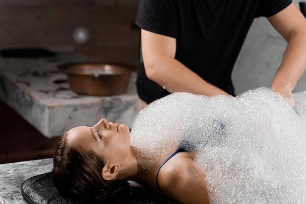 Procedura di spa hammam turco. massaggio peeling con schiuma per il corpo.