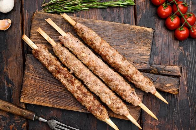 Set di kebab di carne turca, su tavola da portata, su vecchio sfondo di tavolo in legno scuro, vista dall'alto piatta