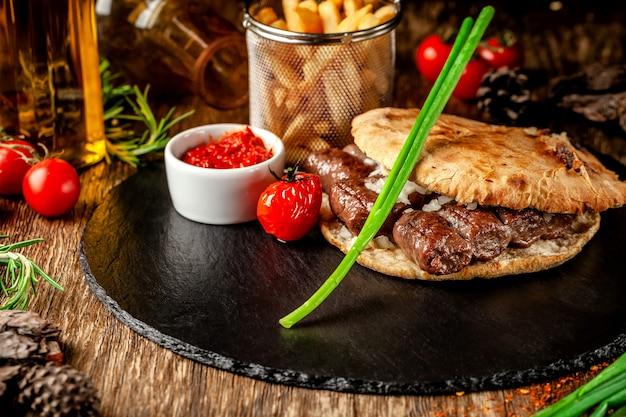Cucina turca, orientale. tortilla turca, panino, pane pita con kebab e cipolle sottaceto. servire in un ristorante su una lavagna nera, su un tavolo di legno