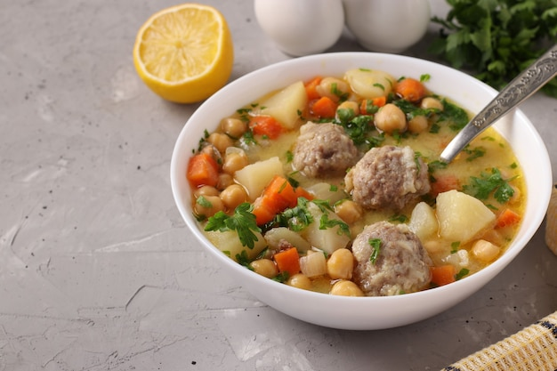Zuppa turca con ceci, polpette e verdure in una ciotola bianca su sfondo grigio.