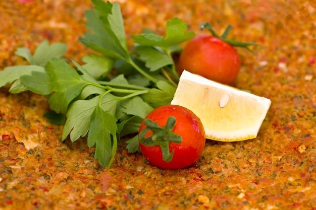 Tortilla turca pita con carne macinata e spezie, con pomodorini e foglie di prezzemolo.