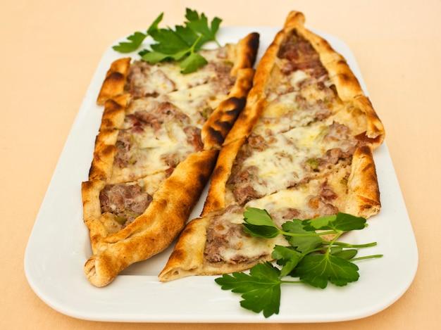 Pita alla tortilla turca con pezzi di carne, formaggio fuso e fette di verdure