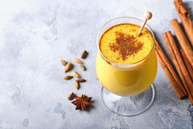 Latte dorato alla curcuma con bastoncini di cannella e miele. bevanda ayurvedica salutare. bevanda disintossicante naturale asiatica alla moda con spezie per vegani. copia spazio.
